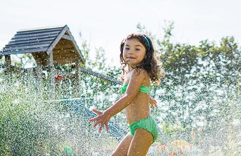 Girl jumping through sprinkler on the lawn