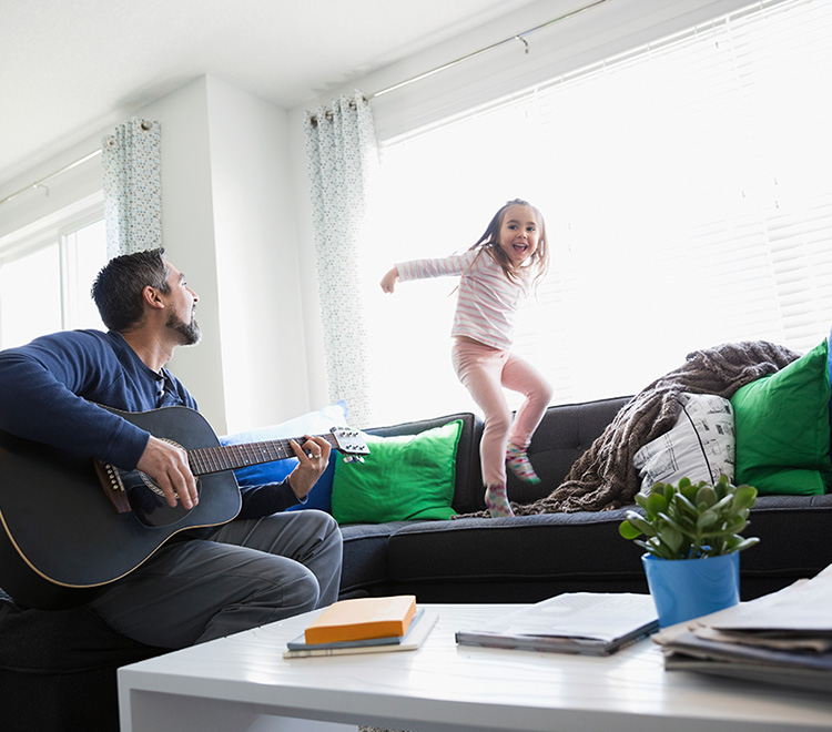 Father playing guitar while daughter dances on sofa
